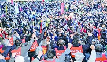 オスプレイ配備撤回を求めてガンバローをする「ノーオスプレイ東京集会」の参加者=27日、東京・日比谷野外音楽堂
