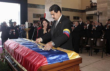 8日、カラカスで行われた故チャベス大統領の国葬で、ひつぎに金色の剣を供えるマドゥロ副大統領(AFP=時事)