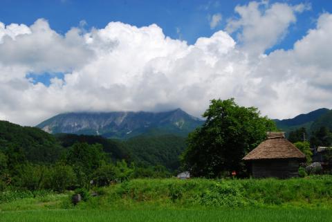 萱葺き屋根の小屋と大山