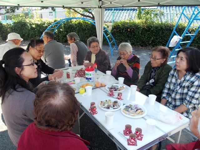 奥で男性同士の交流会。女性陣はお茶菓子を囲んで話に花が咲きます。