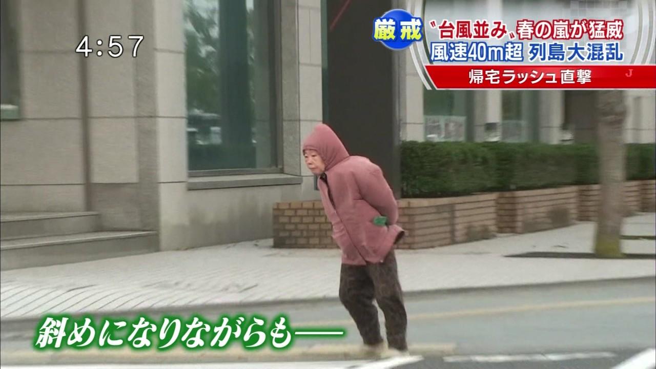 台風の強風で斜めになりながらも歩くお婆ちゃん