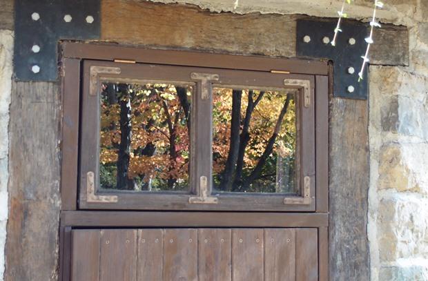 小屋の窓に映り込む紅葉はじめ