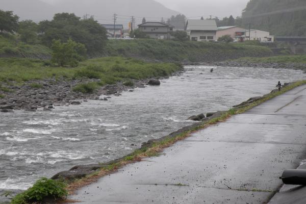 雨の中ドウマンの瀬で釣りをする人