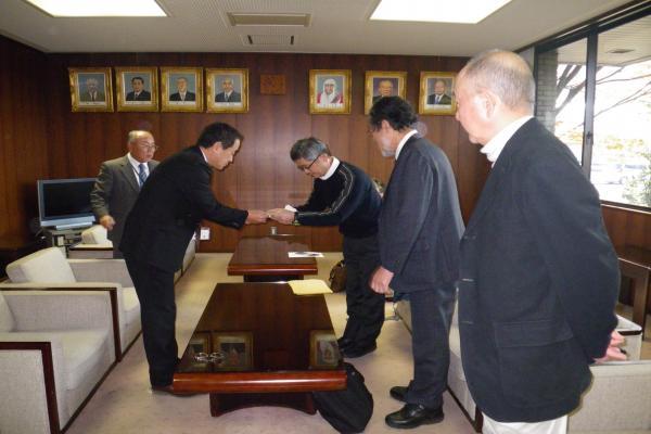 挨拶を交わす堀正安八町長と粕谷代表(右中央)とメンバー