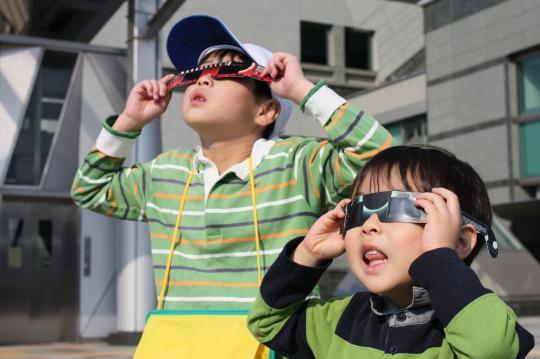 金環日食を見る二人