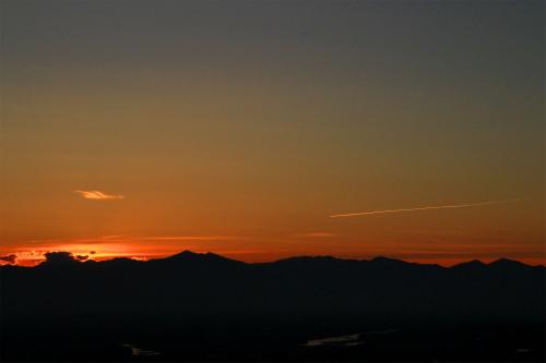 日高山脈に沈む夕陽と飛行機雲