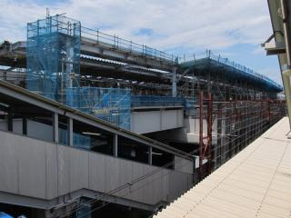 上下線ホームの連絡跨線橋から建設中の高架上りホームを見る