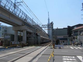 京成曳舟駅前にある京成曳舟1号踏切〈明治通り〉から押上方を見る。中央には東京スカイツリー。