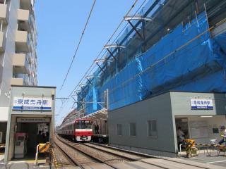 同じ踏切から京成曳舟駅のホームと建設中の高架橋を見る。