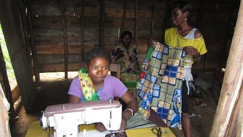 小さな洋裁店で服を仕立てる紛争被害者の女性。