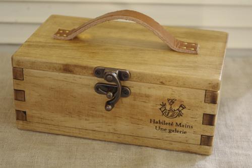 革の持ち手と留め金が付いた木製収納ボックス